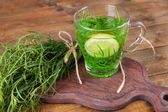 Estragon drink with lemon on cutting board on wooden background — Stock Photo