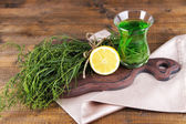 Estragon drink with lemon on cutting board on napkin on wooden background — Stock Photo