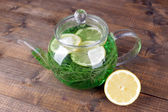 Estragon drink with lemon in teapot on wooden background — Stock Photo