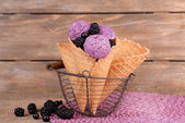 Tasty ice cream with berries in waffle cone on brown wooden background — Stock Photo