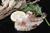 Fresh tasty prawns with lemon, bay leaves and dill on black background — Stock Photo