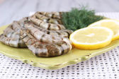 Square plate of prawns with dill and lemon on a yellow napkin on grey wooden background — Stockfoto