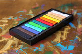 Colorful chalk pastels in box on wooden background — Stock Photo