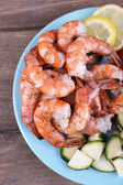 Plate of fresh boiled prawns with tomatoes, lettuce, lemon and avocado on a napkin on wooden background — Stock Photo