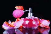 Perfume bottle with petals isolated on black — Stock Photo