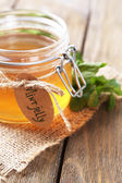 Homemade mint jelly in glass jar, on wooden background — Stock Photo