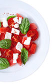 Salad with watermelon, feta and basil leaves on plate, isolated on white — Stock Photo