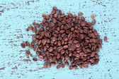 Coffee beans on blue wooden background — Stock Photo