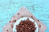 Coffee beans in white plate on sacking napkin on blue wooden background — Stock Photo