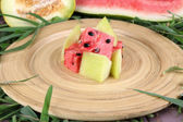 Melon and water melon on bamboo plate on grass on natural background — Stock Photo