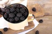 Sweet blackberries in color mug and tasty jam on  wooden background — Stockfoto