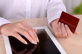 Female hands holding credit card and computer tablet on table on close up — Stock Photo