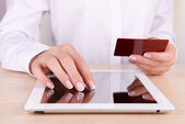 Female hands holding credit card and computer tablet on table close up — Stock Photo