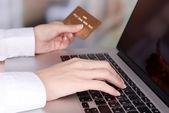 明るい背景上のテーブルにクレジット カードとラップトップを保持している女性の手 — ストック写真