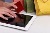 Female hands holding credit card with computer tablet and paper bags on table close up — Stock Photo