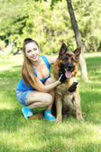 Beautiful young girl with dog in park — Stok fotoğraf