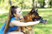 Beautiful young girl with dog in park — Stock Photo