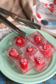 Ice cubes with raspberry on plate, on color wooden background — Stock Photo