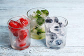 Ice cubes with mint leaves, raspberry and blueberry in glasses, on color wooden background — Stock Photo