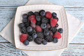 Frozen berries on color wooden background — Photo