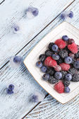 Frozen berries on color wooden background — Stock Photo