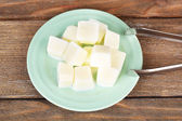 Milk ice cubes on plate on wooden background — Stock Photo