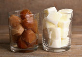 Iced coffee and milky cubes in glass on wooden background — Stock Photo