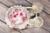Ice cubes with rose flowers in glass bucket and two glasses with champagne on wooden table background — Stock Photo