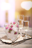 Ice cubes with rose flowers in glass bucket and two glasses with champagne on wooden table, on bright background — Stock Photo