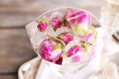 Ice cubes with rose flowers in glass bowl and two glasses with champagne on wooden table background — Stock Photo