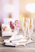 Ice cubes with rose flowers in glass bowl and two glasses with champagne on wooden table, on bright background — Stock Photo