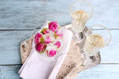 Ice cubes with rose flowers in glass bowl and two glasses with champagne on wooden table, on light background — Stock Photo