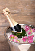 Frozen rose flowers in ice cubes and champagne bottle in bucket, on wooden background — Stock Photo