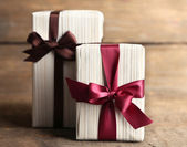Gift boxes with colorful ribbon on wooden background — Stock Photo