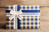 Gift box with colorful ribbon on wooden background — Stock Photo