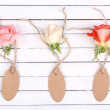 Beautiful roses and empty tags on white wooden background — Stock Photo #51443847