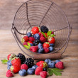 Ripe sweet different berries in metal basket, on old wooden table — Stock Photo