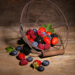 Ripe sweet different berries in metal basket, on old wooden table — Stock Photo #51446361