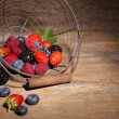 Ripe sweet different berries in metal basket, on old wooden table — Stock Photo #51446371
