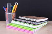 School supplies on table on dark background — Stock Photo