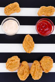 Fried chicken nuggets and sauces on striped background — Zdjęcie stockowe