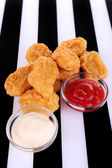 Fried chicken nuggets and sauces on striped background — Stock Photo