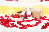 Romantic still life with strawberry, gift boxes and petals of roses on bed — Stock Photo