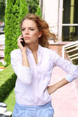 Businesswoman with mobile phone on city street — Stock Photo