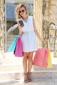 Beautiful young woman with shopping outdoors — Stock Photo