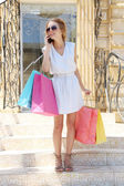 Beautiful young woman with shopping near boutique — Stock Photo