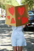 Beautiful young girl with valentines on city street — Stockfoto