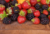 Blackberries and strawberries on wooden background — Stock Photo