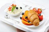 Delicious breakfast with croissant, cottage cheese and fruits — Stock Photo