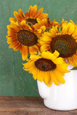 Beautiful sunflowers in pitcher on table on wooden background — Stock Photo